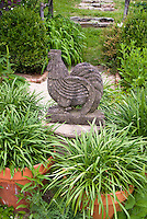 Rooster chicken statue in container garden, using old antiques and flea market finds in the garden