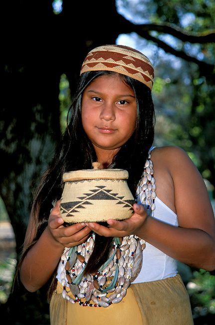Close-up shot of a traditional Yurok girl; (11yrs old); wearing a traditional multi-strand beaded shell necklaces and a basket woven hat. Jene holds a traditionally woven grass basket with lid. Hoopa Valley Indian Reservation California