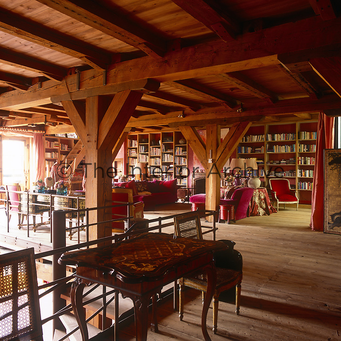 A country sitting room with a heavily beamed ceiling and red walls. The room is furnished with seating upholstered in magenta pink fabric and other period pieces. One wall is taken up with floor to ceiling book shelves.
