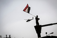 In this Friday, Jul. 05, 2013 photo, an opposition supporter waves an Egyptian flag as an army helicopter flies over Tahrir Square to celebrate the military's coup in Cairo, Egypt. (Photo/Narciso Contreras).