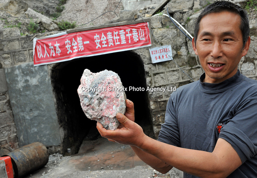 Mr Cao holds a piece of mercury ore at the entrance to the newly opened mine belonging to Yin Ye Mining Co Ltd, in Luoxi Mercury Mining Area, near Wanchuan, Guizhou, China..