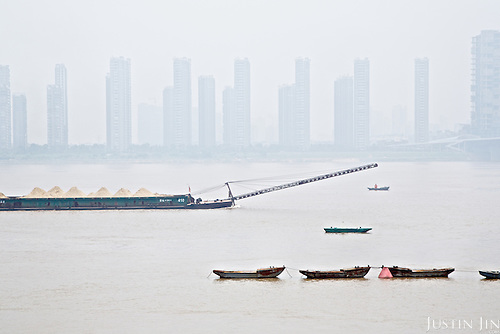 Modern tall buildings rise out of farmland along a river in southern China. <br /> <br /> China is pushing ahead with a dramatic, history-making plan to move 100 million rural residents into towns and cities over six years &mdash; but without a clear idea of how to pay for the gargantuan undertaking or whether the farmers involved want to move.<br /> <br /> Moving farmers to urban areas is touted as a way of changing China&rsquo;s economic structure, with growth based on domestic demand for products instead of exporting them. In theory, new urbanites mean vast new opportunities for construction firms, public transportation, utilities and appliance makers, and a break from the cycle of farmers consuming only what they produce.<br /> <br /> Urbanization has already proven to be one of the most wrenching changes in China&rsquo;s 35 years of economic reforms. Land disputes rising from urbanization account for tens of thousands of protests each year.