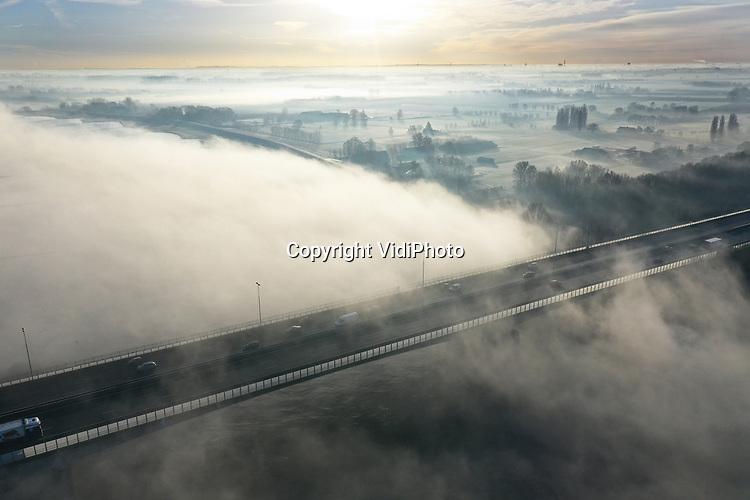Foto: VidiPhoto<br /> <br /> HETEREN – Het was even schrikken vrijdagmorgen voor automobilisten op de A50 ter hoogte van Renkum en Heteren. Een dikke en hardnekkige nevel in het Betuwse rivierengebied en boven de Rijn zorgde tijdelijk voor minder zicht tijdens de spits. Omdat het vrijdagsmorgens minder druk is op de weg, zorgde dat niet voor grote hinder. Wel voor een mooi plaatje vanuit de lucht, met zicht op het viaduct over de Rijn bij Heteren. Nu het 's nachts gaat vriezen en het ook overdag een stuk kouder wordt, is de kans op mist en nevel in de ochtend de komende week vrij groot.