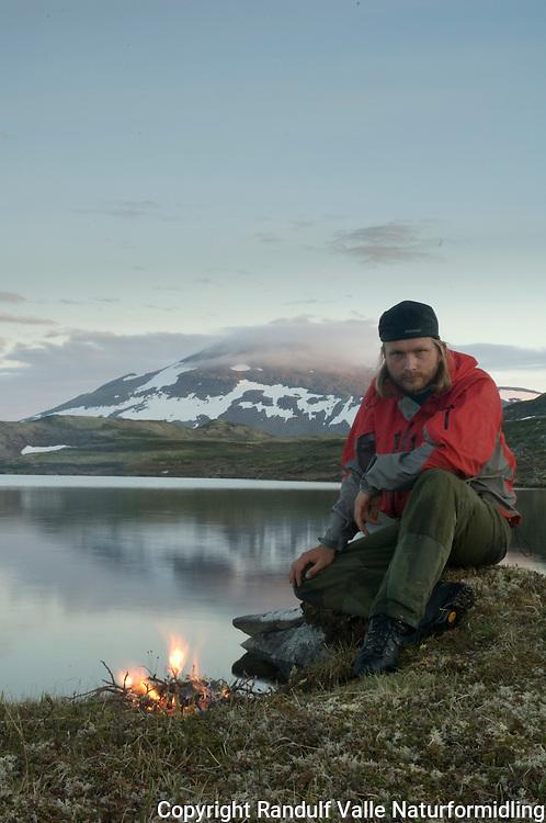 Mann fyrer bål ved Forollsjøen med Forollhogna i bakgrunnen ---- Man and cam fire by lake Forollsjøen