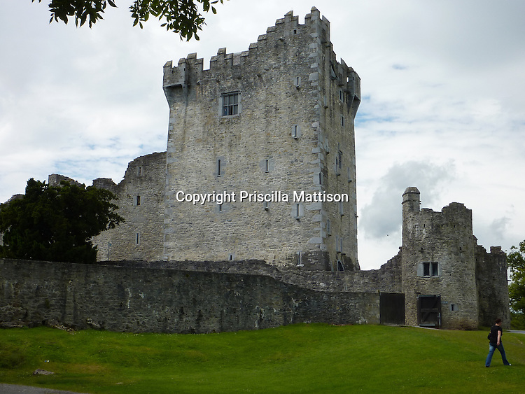 County Kerry, Republic of Ireland - July 19, 2010:  A man crosses the lawn in front of Ross Castle.