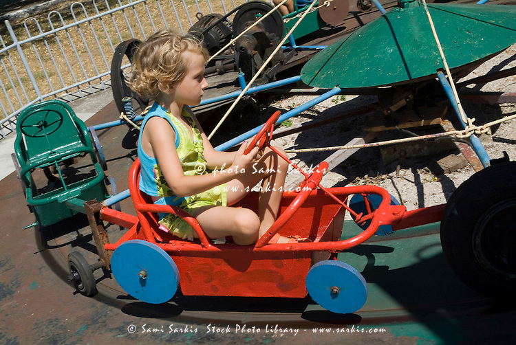 Little girl driving a car on a merry go round ride in Remedios Amusement Park, Cuba.