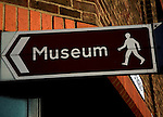 Museum sign pointing direction by foot