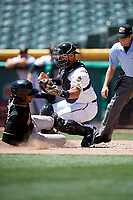 Tony Sanchez (27) of the Salt Lake Bees on defense as a sliding Rosell Herrera (7) of the Albuquerque Isotopes tries to make it under the tag in Pacific Coast League action at Smith's Ballpark on June 11, 2017 in Salt Lake City, Utah. The Bees defeated the Isotopes 6-5. (Stephen Smith/Four Seam Images)