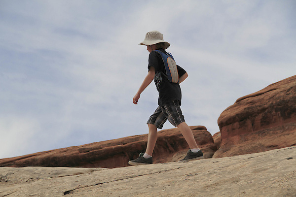 Boy hiking on slickrock in Devil's Garden area, Arches National Park, Utah, USA. .  John offers private photo tours in Arches National Park and throughout Utah and Colorado. Year-round.