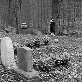 Bruno, West Virginia.USA.January 16, 2005..A tiny lone cemetery guarded over by a Christ figure.