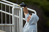 Kannapolis Intimidators assistant general manager Vince Marcucci paints the railings at Intimidators Stadium during the NCAA baseball game between the Mars Hill Lions and the Queens Royals on March 30, 2019 in Kannapolis, North Carolina. The Royals defeated the Bulldogs 11-6 in game one of a double-header. (Brian Westerholt/Four Seam Images)
