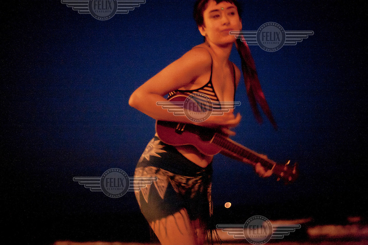 A woman strums on an ukulele on Rockaway Beach, New York. Made famous by the classic song by The Ramones, it stretches for miles along the Atlantic Ocean, while still staying within the borders of New York City.