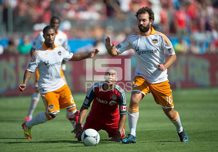 28 July 2012: Toronto FC midfielder Reggie Lambe #19 battles with Houston Dynamo midfielder Adam Moffat #16 and Houston Dynamo defender Corey Ashe #26 during an MLS game between Toronto FC and the Houston Dynamo at BMO Field in Toronto,Ontario Canada...