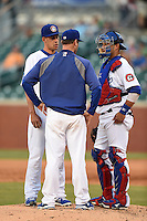 Chattanooga Lookouts pitching coach Scott Radinsky (36) talks with pitcher Carlos Frias (52) and catcher J.C. Boscan (15) during a game against the Birmingham Barons on April 24, 2014 at AT&T Field in Chattanooga, Tennessee.  Chattanooga defeated Birmingham 5-4.  (Mike Janes/Four Seam Images)