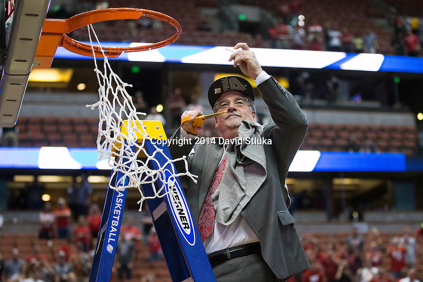 Wisconsin Badgers athletic trainer Henry Perez-Guerra cuts down a piece of the net after the Western Regional Final NCAA college basketball tournament game against the Arizona Wildcats Saturday, March 29, 2014 in Anaheim, California. The Badgers won 64-63 (OT). (Photo by David Stluka)
