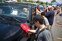 NWA Democrat-Gazette/CHARLIE KAIJO Kennedy Smith of Bentonville (center) watches as students and faculty from Lincoln Jr. High School wash her jeep, Sunday, August 5, 2018 at the parking lot of Sport Clips in Bentonville. <br />