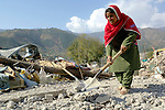 Bibi Rahiba, who lost her husband, brother, and three children to the October 8, 2005, earthquake, digs into the rubble of her home in search of their bodies.