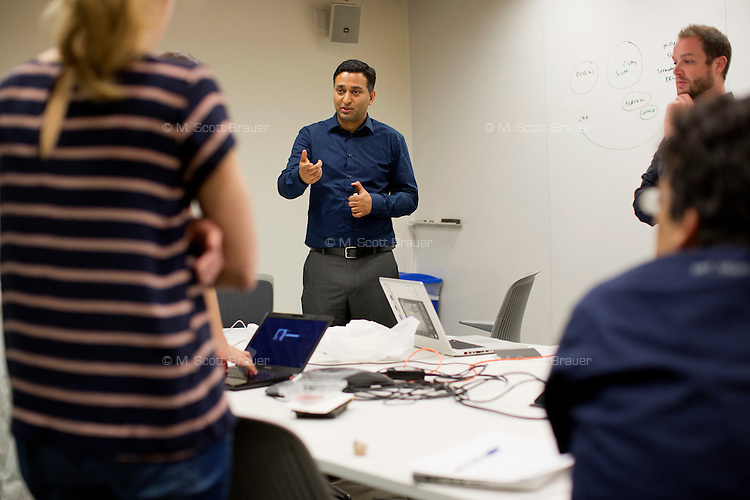 Professor Ramesh Raskar (blue) leads his Camera Culture group in a meeting to discuss an upcoming Hackathon in India. Raskar is the director of the Camera Culture group at MIT's Media Lab.