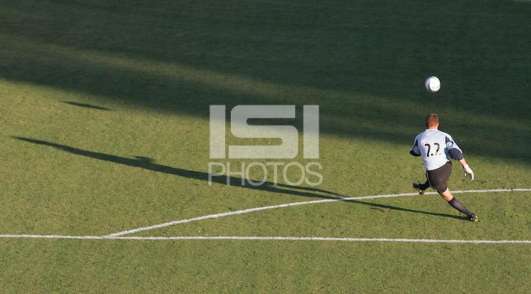 Goalie kicking soccer ball.