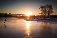 An ice skater skates on Westchester Lagoon at sunsrise in midtown Anchorage.  Winter  Chugach Mountains are in the background.