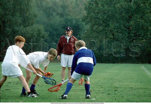 A male coach instructing a class of boys, Children's Lacrosse, South London, 9511. Photo: Glyn Kirk/Action Plus...1995.teach teaching teacher teachers.coaching coaches.tuition.tutor.instructor instruction.trainer training.school.child.children.kids.boy.boys.Youngster.Youngsters.childrens sport.children's sport.lesson learn learning