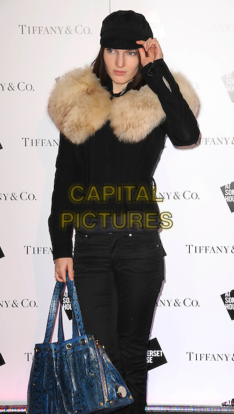 BEN GRIMES .Somerset House Ice Rink - Arrivals, London, England, November 18th 2008..half length hand on hat cap black coat jacket fur collar blue bag jeans snakeskin print patent .CAP/CAS.©Bob Cass/Capital Pictures