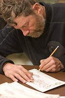 Musher  Jim Lanier signs mail caches before the start of the All Alaska Sweepstakes dog sled race in Nome, Alaska.