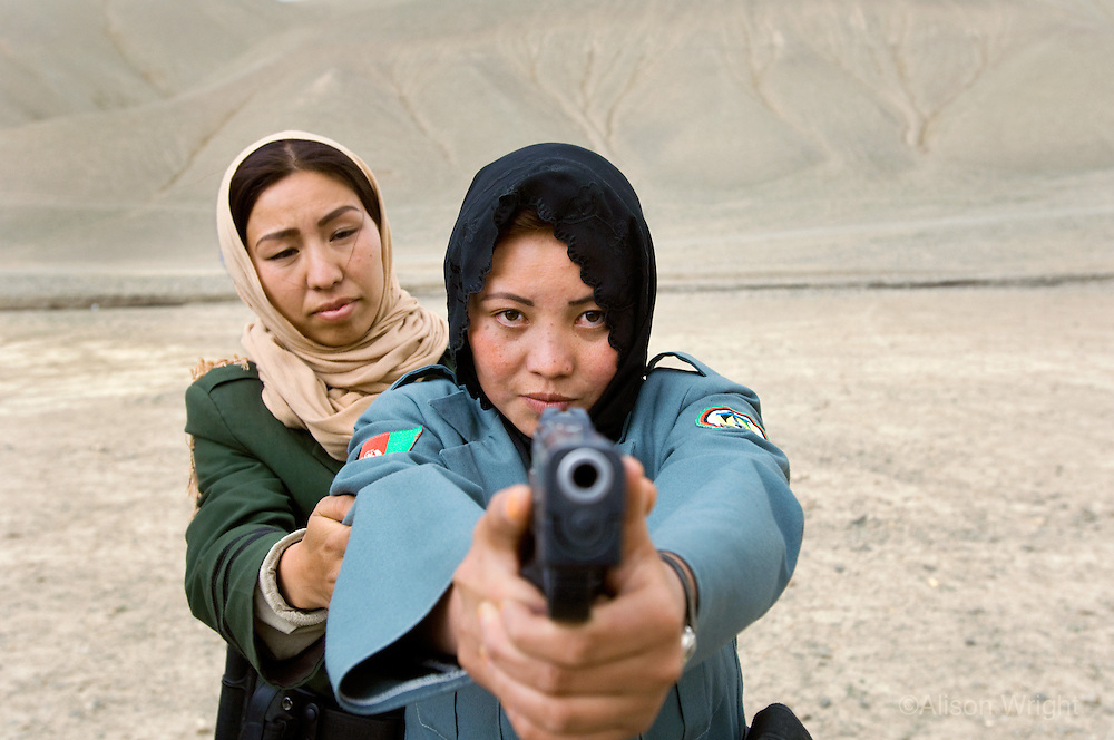 Women police officers practicing at shooting range.
