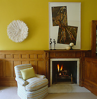 A fireplace positioned unusually in a corner of the bright yellow library