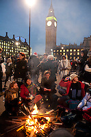 Protestors make a fire to keep warm on Parliament Square outside the Houses of Parliament during a student demonstration in Westminster, central London on the day the government passed a bill to increase university tuition fees.