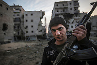 Hassan, a sixteen years old rebel fighters, poses for photo at Al Amiriyah neighborhood, a battlefield southwest of Aleppo, Syria.