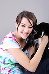A young teen holding a domestic black cat