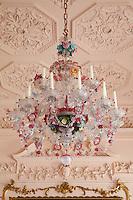 Underneath the lavish, leafy scrolls of a rococo celing hangs an extravagant eighteenth century Murano chandelier
