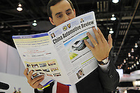 A man reads a copy of the China Automotive Review from the display for Chinese-made car Build Your Dreams, BYD, at the Detroit Auto Show in Detroit, Michigan on January 11, 2009.