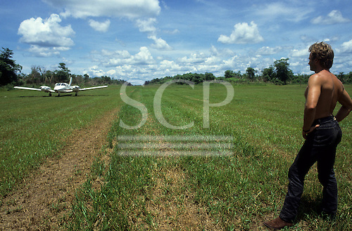 Pavuru Village, Brazil. Sting standing beside a grass airstrip with a small plane; Xingu, Nov 1990.