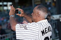 Former Charlotte Hornet Minnie Mendoza takes a photo of the Charlotte skyline with his smart phone prior to the International League game between the Durham Bulls and the Charlotte Knights at BB&T BallPark on May 16, 2017 in Charlotte, North Carolina.  The Knights defeated the Bulls 5-3. (Brian Westerholt/Four Seam Images)