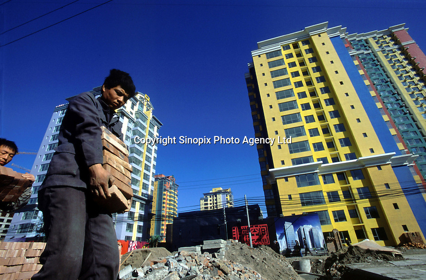 Workers convey bricks at the worksite of an apartment compound in Beijing, China..