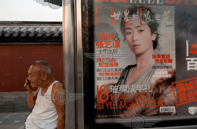 An old man sitting next to advertising at a bus stop for the Chinese edition of the fashion magazine Elle.