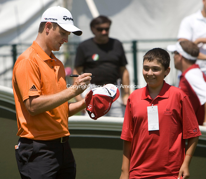 CROMWELL, CT - 23 JUNE 2010 -062310JT13-<br /> Golfer Justin Rose signs the hat of an eager young fan at the 1st tee during Wednesday's Travelers Celebrity Pro-Am golf event at TPC River Highlands in Cromwell.<br /> Josalee Thrift Republican-American