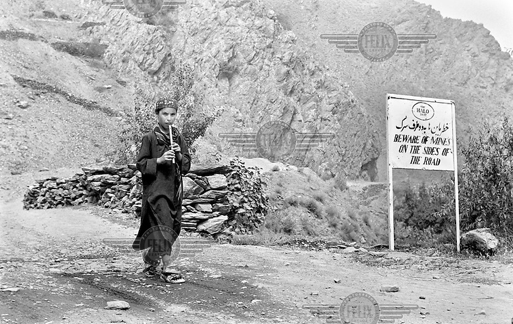 Recently returned from growing up as a refugee in Iran, a boy plays the flute as he walks past a minefield near Bamiyan, Aghanistan on June 26, 2002. More than six million people fled Afghanistan during the years of conflict following the Soviet invasion in 1979.