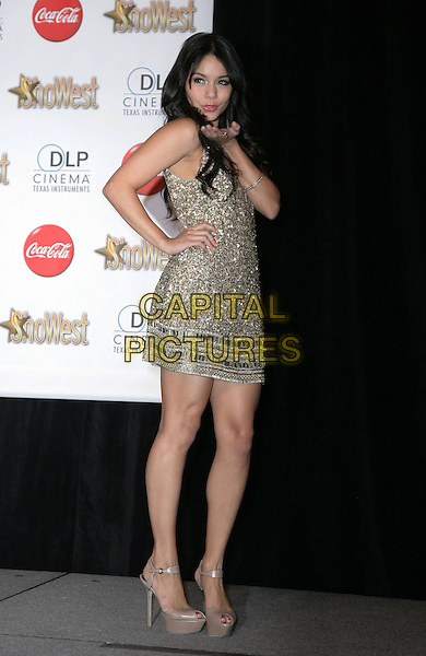 VANESSA HUDGENS .SHOWEST Final Night Talent Awards at the Paris Resort Hotel and Casino,  Las Vegas, Nevada , USA,.18th March 2010..full length gold beaded jewel encrusted embellished dress hand on hip brown peep toe platform shoes ankle strap blowing kiss gesture .CAP/ADM/MJT.© MJT/AdMedia/Capital Pictures.