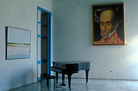 Cuba, Havana, piano in an empty room with a large portrait hanging on the wall