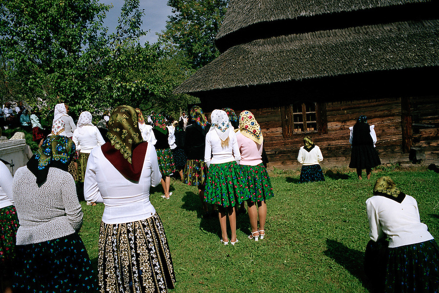 ROMANIA / Maramures / Budesti / September 2006..Women attending Romanian Orthodox Church services on a sunday morning outside the traditional wooden upper church dating from 1586. Most Maramures villages have 2 churches placed at either end and the region is famous for them, many of which are on the UNESCO World Heritage list. ..© Davin Ellicson / Anzenberger