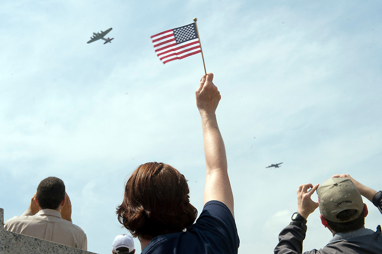 UNITED STATES - MAY 8: A spectator waves to World War II era aircraft as they fly over the World War II Memorial on the Mall to commemorate the 70th anniversary of the victory in Europe, known as VE Day, May 8, 2015. (Photo By Tom Williams/CQ Roll Call)