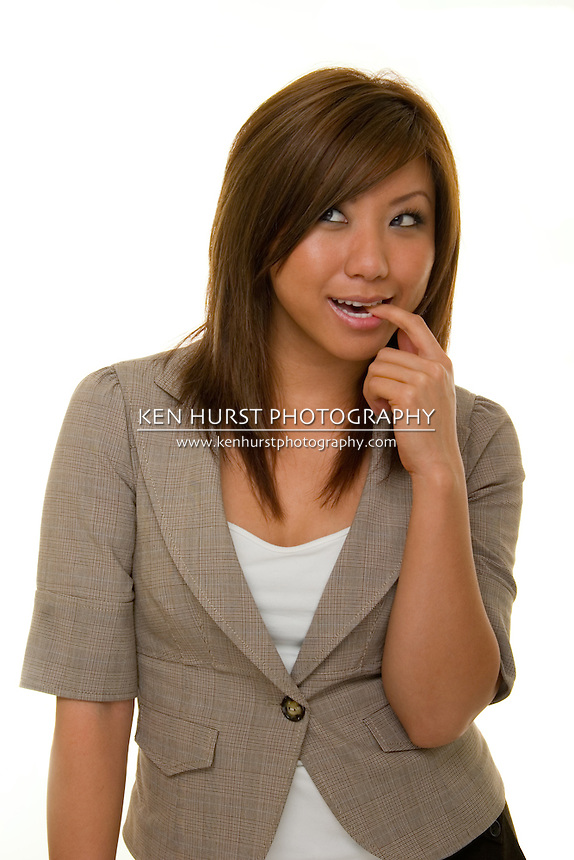 Beautiful young Asian business woman in business suit thinking.