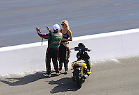 Sept. 15, 2012; Concord, NC, USA: NHRA funny car driver John Force (left) talks with daughter Courtney Force during qualifying for the O'Reilly Auto Parts Nationals at zMax Dragway. Mandatory Credit: Mark J. Rebilas-