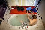 University of California, Merced student Jaron Brandon writes a term paper from the comfort of a whirlpool tub of his master suite in the spacious rental home he shares in Merced, Calif., October 29, 2011.