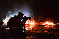 Press-photographer reporting from the barricades during protests. Kiev, Ukraine. Jan. 22, 2014. (Photo by Msyslav Chernov / UnFrame)