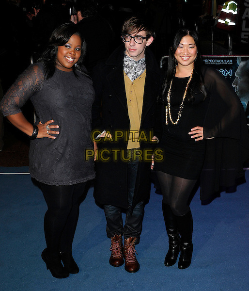 "AMBER RILEY, KEVIN McHALE & JENNA USHKOWITZ .At the ""Tron: Legacy"" UK Film Premiere, Empire cinema, Leicester Square, London, England, UK, .December 5th 2010..full length glee cast black dress grey gray lace jeans coat glasses hand on hip .CAP/CAN.©Can Nguyen/Capital Pictures."