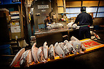 Tokyo, 1st of March 2010 - Tuna at Tsukiji wholesale fish market, biggest fish market in the world. 6:15 a.m, a middleman has its frozen tunas cut in small pieces after the auctions.